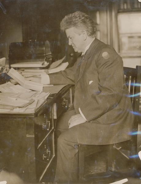 Senator Robert M. La Follette Sr., posed sitting at his desk reading a letter.