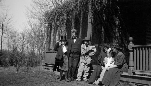 Robert M. La Follette, Sr., at Maple Bluff Farm with three of his children, Philip F. La Follette, Robert M. La Follette, Jr., and Mary, all of whom are dressed in costume.  Mrs. La Follette is seated on the porch steps (half hidden) and with her is Nellie Dunn, the secretary in La Follette's law office.