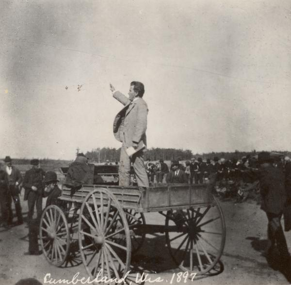"Robert M. La Follette, Sr., with his fist in the air, speaking from the back of a wagon. It was in part due to his vigorous speaking style that La Follette won the nickname ""Fighting Bob."" This image is one of a series of views of his appearance at a fair in Cumberland, Wisconsin, in 1897. After three unsuccessful campaigns during which he brought his reform message to Wisconsin at events such as this, La Follette was elected governor of Wisconsin in 1900."