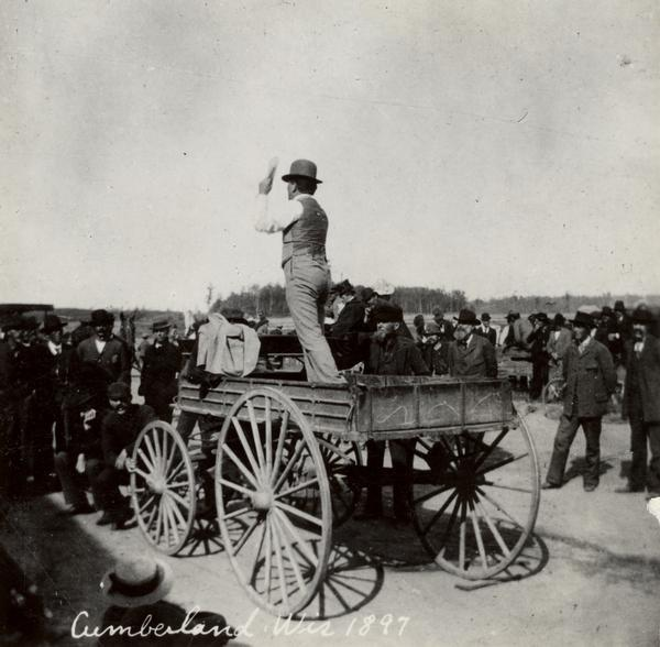"Robert M. La Follette, Sr., with his fist in the air, speaking from the back of a wagon. He is wearing a hat and a suit without the coat. It was in part due to his vigorous speaking style that La Follette won the nickname ""Fighting Bob."" This image is one of a series of views of his appearance at a fair in Cumberland, Wisconsin, in 1897. After three unsuccessful campaigns during which he brought his reform message to Wisconsin at events such as this, La Follette was elected governor of Wisconsin in 1900."