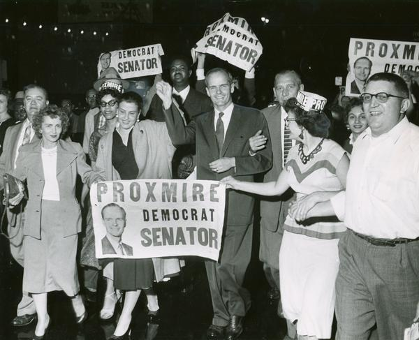 "William Proxmire, his wife, Ellen (to Proxmire's right), and his supporters celebrate his victory in the special election to fill the Senate seat vacated upon the death of Senator Joseph R. McCarthy. The supporters carry signs that read ""Proxmire Democrat Senator""."