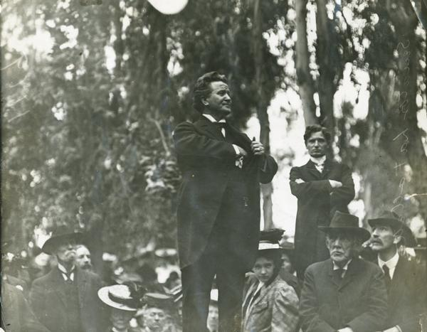 Senator Robert M. La Follette, Sr., addressing a crowd in a Los Angeles park.  This view, which is similar to ID# 30219, shows La Follette reaching into his pocket, perhaps for a handkerchief, and shows some of his audience.
