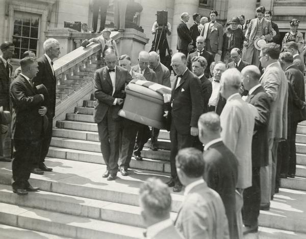 Pallbearers (who include Senator Herman Ekern), carry the flag draped casket of Senator Robert M. La Follette, Sr., down the steps of the Wisconsin Capitol to the waiting hearse.  In the background are Robert M. La Follette, Jr., Belle Case La Follette, and Philip Fox La Follette.