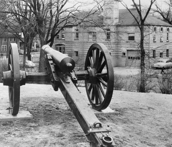 A Civil War cannon captured at the Battle of Shiloh, displayed at Camp Randall near the corner of Randall Street and Dayton Street.  A fire station is visible in the background.
