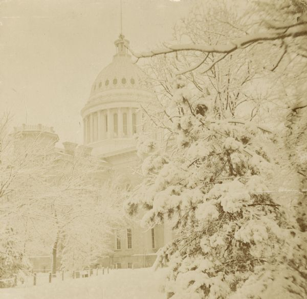 Winter scene of the Wisconsin State Capitol with snow-covered trees.