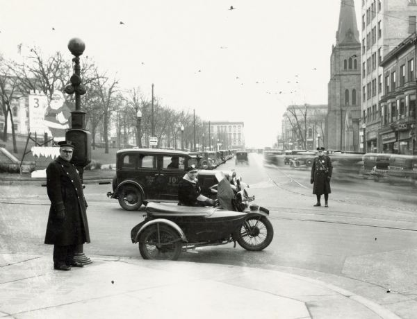 Two police officers, one on a motorcycle with sidecar on the corner of Mifflin and Carroll Street, on the Capitol Square.  A large Santa Claus cutout is located on the corner of the Square.