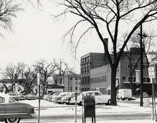 West Doty Street, from Monona Avenue looking toward South Carroll Street, showing the back side of Madison Newspapers, Inc. The building was added on to in 1949 when The Capital Times and Wisconsin State Journal merged.  The new addition housed the press room with the mail room on the second floor. The spiral chute is where the newspaper bundles were sent from the mailing room to the loading dock. The building further down the street is probably the Baskerville Apartments, 121-29 South Hamilton Street.
