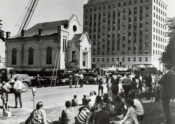 The moving of the Gates of Heaven Synagogue from West Washington Avenue to James Madison Park. Crowds line the streets, and a crane can be seen in the background.
