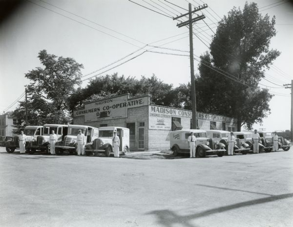 Exterior of the Madison Consumers Dairy Co-operative, probably located at 102 South Dickinson Street, with the milkmen posing next to their home delivery trucks--all Internationals.