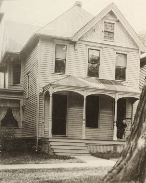 Exterior view of the Merrick residence with a woman sitting on a swing on the front porch.