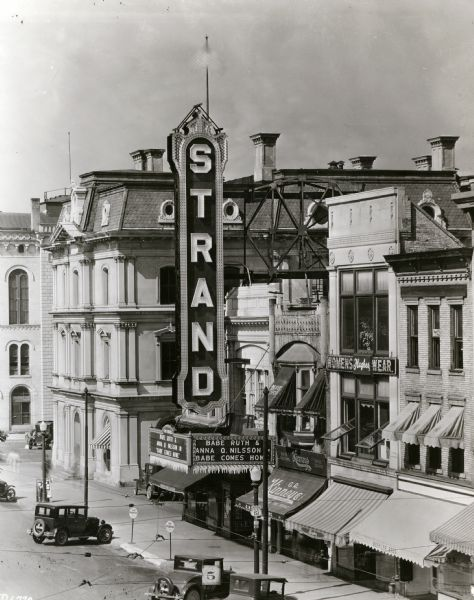 "Elevated view of the Strand Theater located at 16 East Mifflin Street near the corner of Wisconsin Avenue. The marquee reads ""Babe Ruth and Anna Q. Nilsson, Babe Comes Home."" To the left of the theater is an building with an awning that reads: ""Collyer Pharmacy."" Buildings on the right of the theater have signs that read: ""G.R. Kinney Co. Inc. Largest Shoe Retailers,"" ""Hughes Womens Wear,"" ""Buehler Bros. Meats."" A street sign reads: ""WISCONSIN U S 151."""