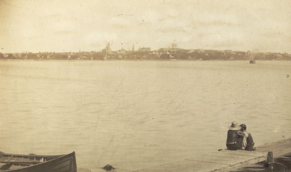 View of Madison from across Lake Monona with couple in foreground on pier.