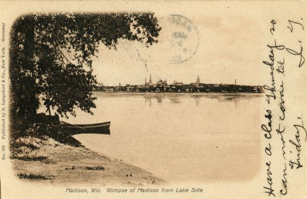 View of Madison from across Lake Monona. A boat floats in the water near the shoreline of the lake in the foreground of the photograph.