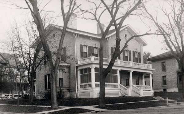 Dr. and Mrs. Philip R. and Katherine B. Fox residence at 28 West Wilson Street, corner of South Carroll Street. The house was constructed of Milwaukee brick and was completed by Peter Young in 1871. He lived there until it was sold to the Foxes in 1903. The residence became a boarding house between 1935 and 1954 when it was demolished.