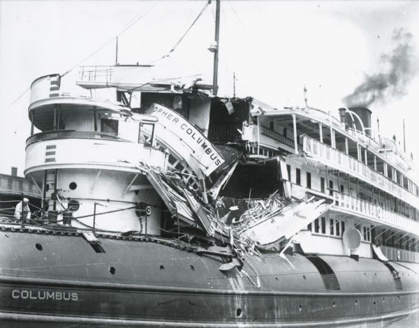 Image of damaged ship on the Milwaukee River. The <i>Christopher Columbus</i> was a popular cruise vessel launched in 1893 and used to traverse the Great Lakes. On June 30th, 1917, with 413 passengers onboard, the ship was being towed out of the Milwaukee River by tugboats when an unexpected and overwhelming current forced the ship toward shore. The ship collided with a water tower and was demolished. Sixteen passengers died and another 20 were hurt in this freak accident. The <i>Christopher Columbus</i> was repaired and put back into service the following year and sailed the lakes for another 19 years before it was scrapped at Manitowoc, in 1936.