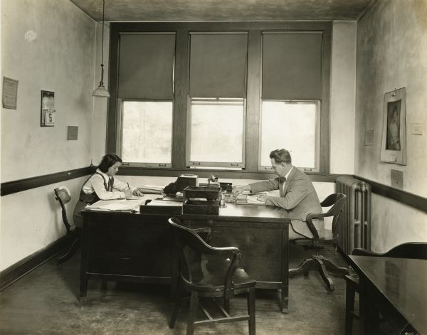 Interior of the company president's office. President Martin P. Winther and a female worker are seated at desks.
