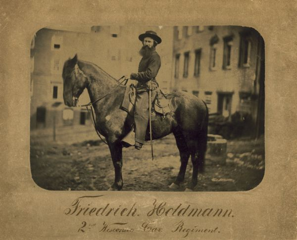 Friedrich Holdmann of the Second Wisconsin Cavalry Regiment during the Civil War, astride his horse. Buildings are in the background.