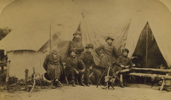 Officers of the Second Wisconsin Infantry posed in front of a tent. They are, from left to right, Quartermaster J.D. Ruggles, Dr. A.J. Ward, Major J.S. Allen (standing), Lt. Colonel Lucius Fairchild, Adjutant C.K. Dean (standing), and Colonel Edgar O'Connor. Fairchild, Dean and O'Connor are clearly wearing the distinctive black hats of the Iron Brigade. The flag of the 2nd can also be seen, unfurled behind them.