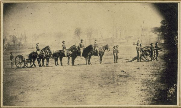 Soldiers of the 3rd Wisconsin Artillery at Camp Randall man a cannon on wheels while other men on foot and on horseback follow.