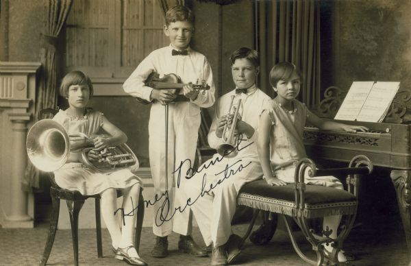 "Four children with their musical instruments. Writing on the picture says ""Honey Bunch Orchestra""."