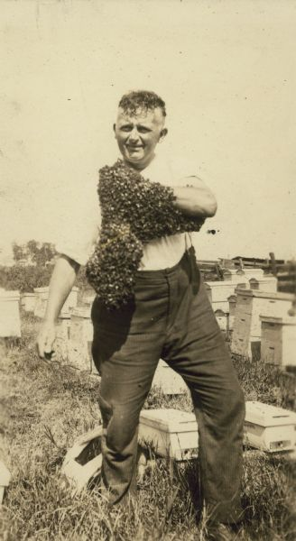 George J. Gunther in a apiary with a swarm of bees covering his left arm.