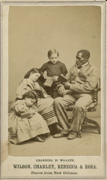 "A carte-de-visite of a slave sitting with three children. The text at the bottom says ""Learning is Wealth. Wilson, Charley, Rebecca, & Rosa. Slaves from New Orleans."""