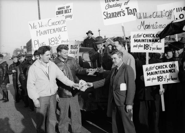 Del Krause, president of Local 1114, United Steelworkers of America (second from left) smiles as he and Ken Gorman, vice-president of the local, hand $800 to Howard Johnson, vice-president, and Sid Ray, president, of striking Chain Belt [Co.] Local 1527.  The gift followed a parade of 1000 Harnischfeger workers to the struck plant.  Wisconsin CIO News.