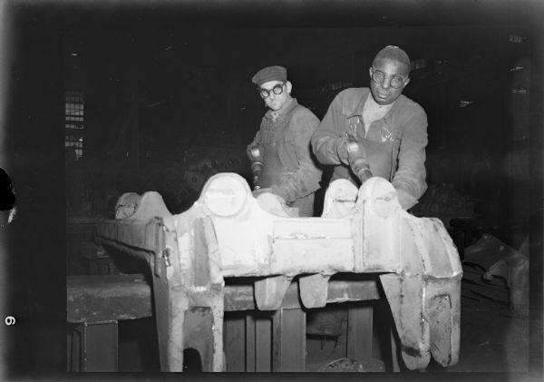 Workers chipping imperfections from a rough casting.