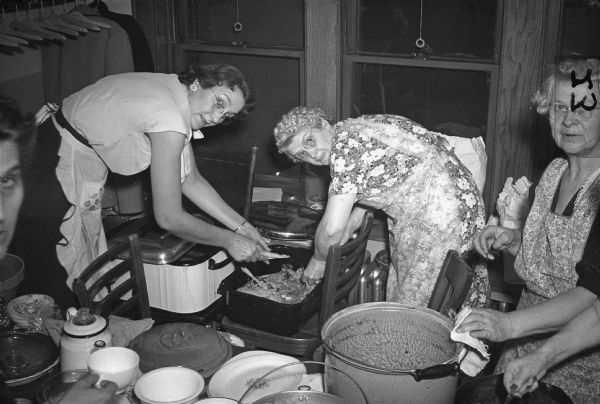 Members prepare a banquet to celebrate the eleventh anniversary of Auxiliary No. 2, United Automobile Workers (Seaman Body Company), October 23, 1946.  Executive board member Laura Miller in flowered dress.