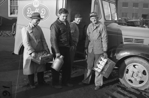 "A driver for Dairy Distributors, Inc. cooperative of Watertown, Wisconsin delivering milk to strikers' soup kitchen.<p>""Several dairies have volunteered to help the United Packinghouse Workers strikers by supplying them with all the milk they need.  Jack Prospect, member of Local 50, is pictured helping to carry in part of the day's supply.""<br>- Wisconsin CIO News</p>"