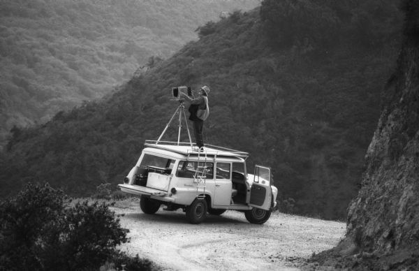 Ansel Adams atop a camera platform on his International Travelall inserts an 8 x 10 film holder into his camera.