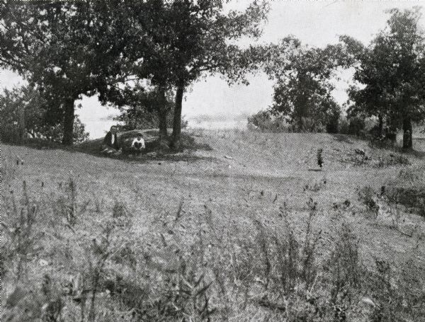 Two men enjoy the shade among Native American burial mounds on the Dividing Ridge, a recessional moraine, between Lakes Monona and Wingra in Madison, Wisconsin.  The Dividing Ridge and the mounds were subsequently destroyed by gravel mining.