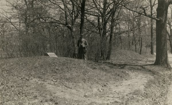Charles E. Brown poses near a historic tablet marking one of a row of conical burial mounds on the Park and Pleasure drive on the north shore of Lake Wingra. These mounds are now incorporated within the Edgewood College campus.
