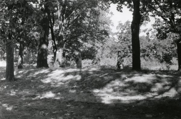Burl Briggs (right), and an unknown companion pose behind a linear burial mound on the University of Wisconsin-Madison campus.