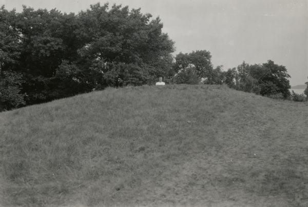 A man poses behind a large conical Native American burial mound near the center of Picnic Point on the University of Wisconsin-Madison campus.