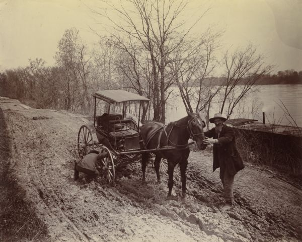 Horse-drawn carriage stuck in a rut on a muddy road near the Ohio River in Floyd County, Indiana. One man is holding the horse while another attempts to dislodge the wheel. This image was entered in a 1898 competition sponsored by the League of American Wheelman to identify the nation's worst roads conditions. The purpose of the competition was to gather evidence of the need for better roads.  The donor, Otto Dorner of Milwaukee, was the national chair of the league's road improvement committee.