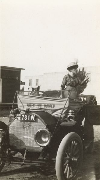 "Suffragist Katherine Waugh McCullough speaking from an open car. A banner on the car reads: ""Votes for Women."""
