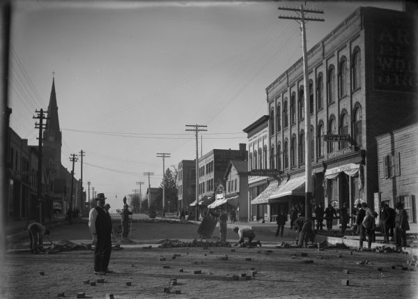 Paving Watertown's main street with bricks, with almost as many men who are watching as construction workers.