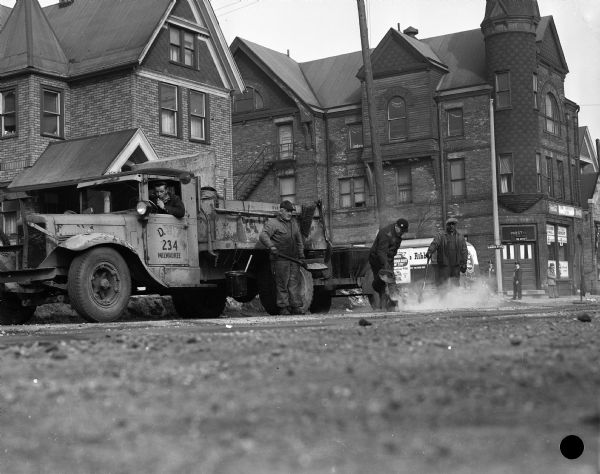 Milwaukee streets department employees repair the intersection of Meinecke Avenue and 12th Street.  Behind them, a Blatz truck is making a delivery to the Wisconsin Hall Tavern.