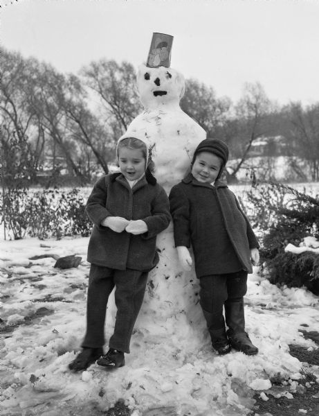 Winter scene with two children leaning against a snowman.