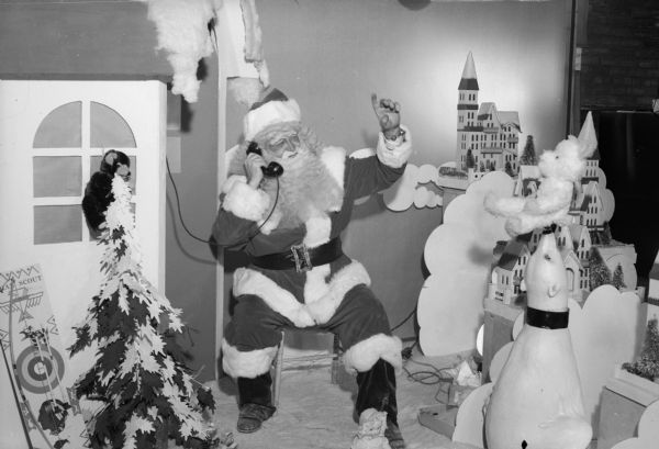 Santa Claus talks on a telephone seated in a Christmas display in Manchester's Department Store.