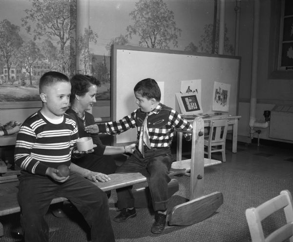 "Patricia Mathisen (Mrs. George), member of Kappa Kappa Gamma sorority alumnae group, sponsor of the Nursery School for Slow Learners at the First Congregational Church, is playing with two boys on a ""rocking train."""