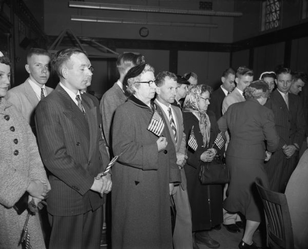 Men and women holding United States flags after a ceremony in the federal courtroom making them naturalized citizens.