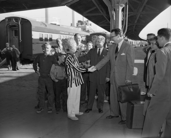 Walt Kelly arriving in Madison at the Chicago & North Western depot, is met by a person dressed as Pogo, one of his cartoon characters.