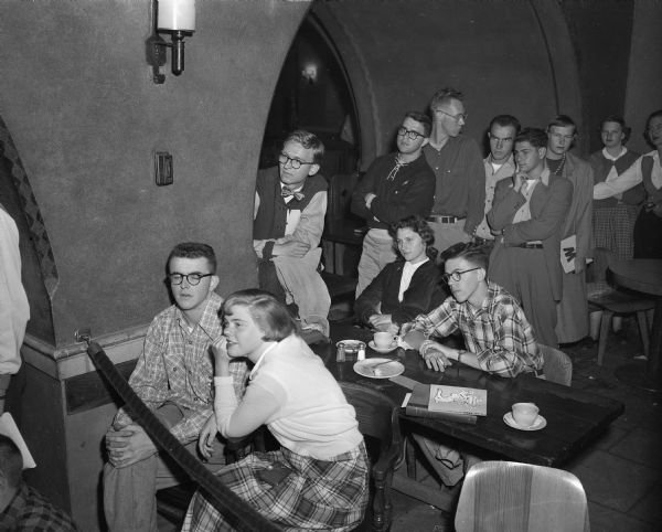 Students in the Rathskeller on the University of Wisconsin campus listening to a presentation by cartoonist Walt Kelly on his book tour.