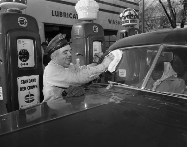 Franz Haas, sheriff elect, washing the windshield of a car at his Standard Gas Station, 318 South Park Street.
