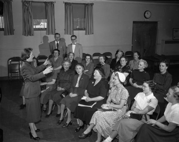 A woman talks to a group of women while two men stand in the background.