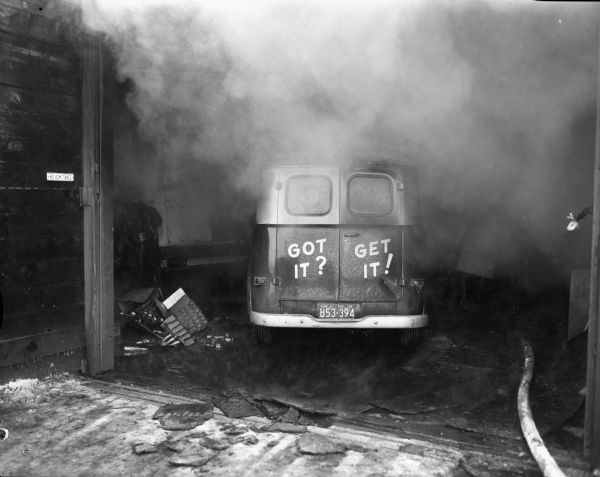 "Rear view of a fire damaged beer delivery truck with ""Got It? Get It!"" painted on its doors.  An exploding oil furnace destroyed the interior of the Madison Beverage Corporation beer depot, 714 East Olin Avenue."
