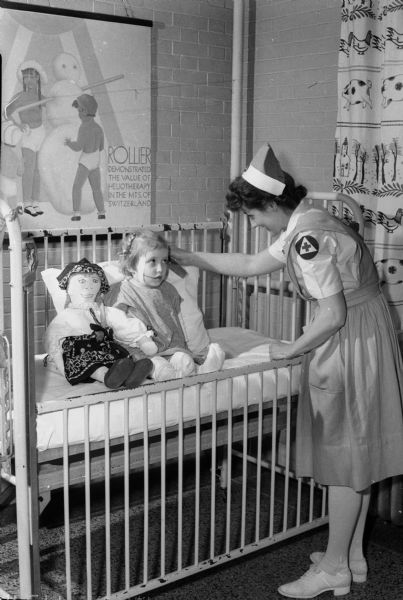 "Mable Sawtelle, a Red Cross nurses' aide, tends to baby Sara in a crib with doll.  Poster says:  ""Rollier demonstrated the value of heliotherapy in the mts. of Switzerland""."