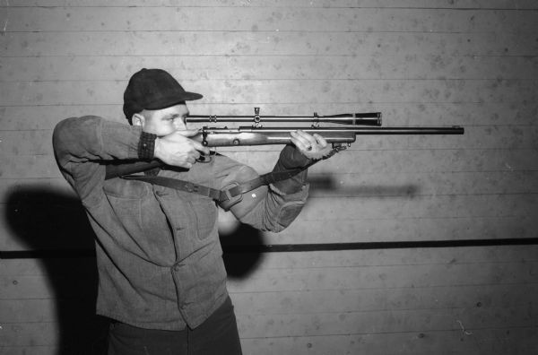 "Paul Haberman, member of the Madison Legion Rifle and Pistol Club, aiming a rifle. The Club is sponsoring the ""Little Worlds Rifle and Pistol Championship Match,"" April 20-27, 1941."